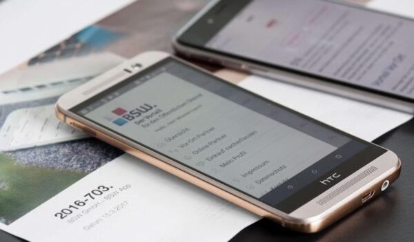 BSW App Screen auf HTC Smartphone daneben zweites Smartphone im Hintergrund ein Katalog