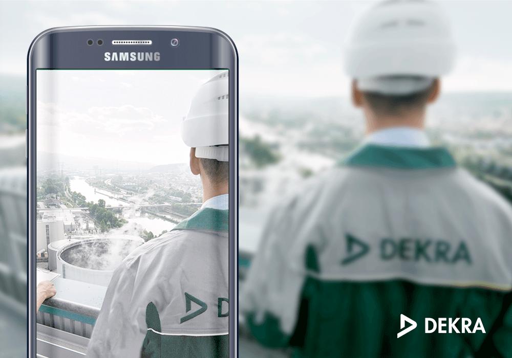 Dekra Logo und Mann mit Dekra Arbeitskleidung auf Samsung Smartphone