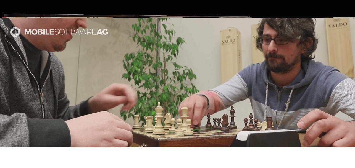 Zwei alte Entwickler Hasen spielen im Teamraum eine Partie Schach gegeneinander