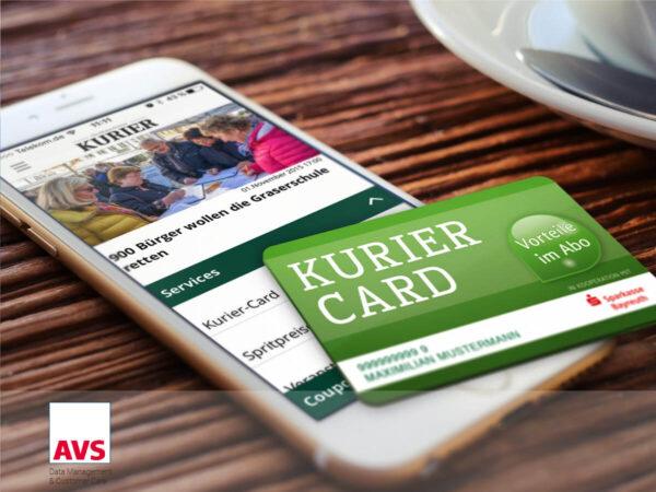 Kurier card der Sparkasse Bayreuth und Kurier App auf iPhone. Beides liegend auf holz tisch neben cafe tasse