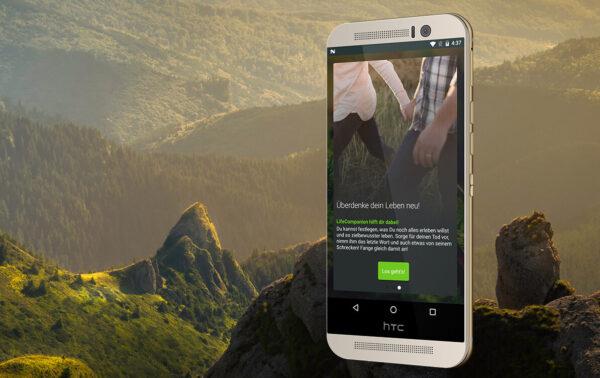 LifeCompanion App auf Smartphone vor idyllischer Landschaft