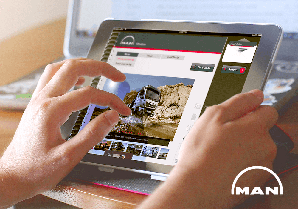 MAN logo und Man News App auf einem Tablet Laptop im Hintegrund