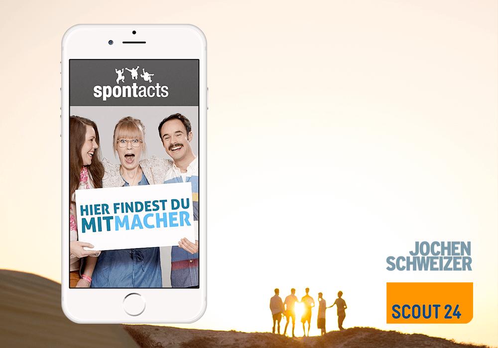 Jochen Schweizer Logo Scout 24 Logo Spontacts App auf iPhone Gruppe von Leuten auf Hügel im Hintergrund