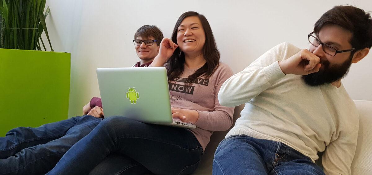 Drei Menschen lachend auf Couch