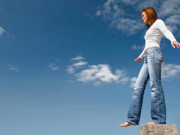 Frau auf einem Bein stehend auf Stein
